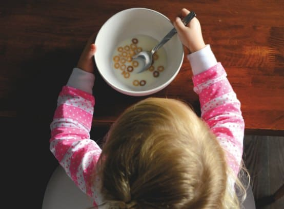 daddy daughter date ideas - little girl eating breakfast cereal from a bowl