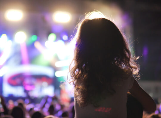 daddy and daughter at a concert, daughter on father's shoulders.