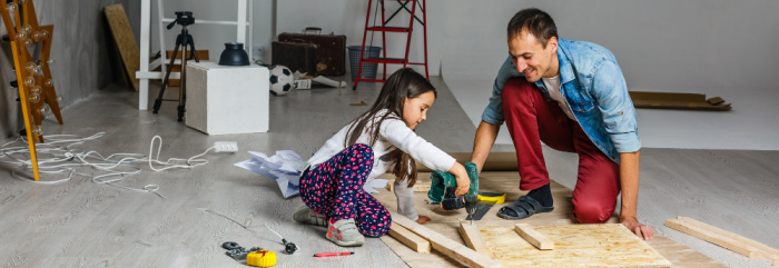 father and daughter doing house repairs in the garage