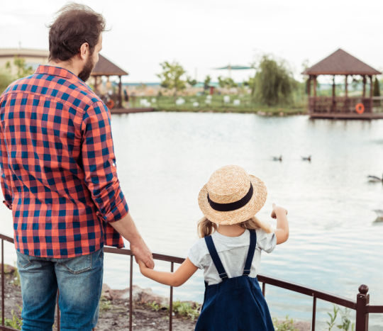 father daughter looking at a pond